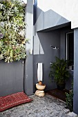 Corner of terrace with vertical planting and outdoor shower in niche