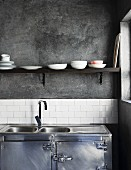 Purist, industrial-style kitchen with stainless steel base unit and sink below simple shelf on grey wall