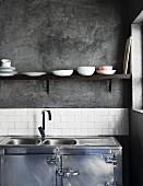 Puristisch gestaltete Küche im Industrie-Stil mit Edelstahl Unterschrank und Spülbecken unter Regalbrett an grauer Wand