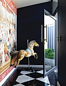 Old carousel horse next to wall with vintage poster in entrance hall with chequered floor and glass door