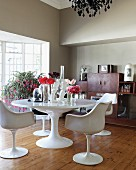 White, classic swivel chairs at round table with vases of flowers and flowers in front of lattice terrace doors in grey-painted living room with simple board floor