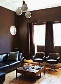 Elegant living room with walls painted dark brown, black leather sofa and swivel chairs around wooden coffee table and Art Deco ceiling lamp