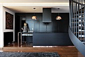 Open-plan, black kitchen and pendant lamps with copper-coloured lampshades in interior with partially visible spiral staircase