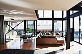 Penthouse apartment with steel and glass facade, comfortable lounge area with leather sofa and dining area