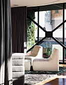 White easy chairs on rug in front of glass facade with dark, floor-length curtains