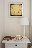 China teacup, books & table lamp on bedside cabinet