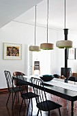 Modern dining room with black dining table below designer pendant lamps; black wood-burning stove in background next to basket of firewood