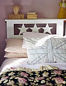 Double bed with star motif, hand-stitched pillow and black floral bedspread