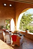 Various armchairs and coffee table on stone-flagged loggia floor and view of sunny garden through rounded arches