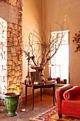 Zimmerecke in herrschaftlichem Landhaus mit rundem Tisch zwischen Bodenvase vor Natursteinpfeiler und roter Chaiselongue