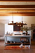 Long foyer with wood-beamed ceiling and collection of hats on shelf suspended above wooden table; contented dogs on rug
