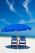 Deckchairs and parasol on beach, Clearwater, Florida, United States