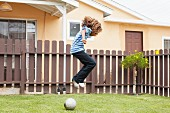 Boy jumping over football