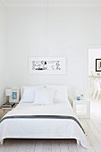 Double bed with white bed linen in minimalist bedroom with open door and view of chairs beyond