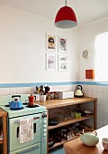 Retro cooker in corner of kitchen with modern, wooden shelves against tiled walls; pendant lamp with red lampshade