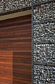 Gabion house facade and door of mahogany-coloured wooden slats