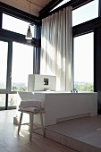 Bathtub on platform in corner of room with glass walls in contemporary house with white curtain in front of window