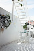 Terrace with white mosaic tiles, white table and chairs and staircase leading to further roof terrace above