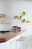Solid wood kitchen counter and plexiglass bar stools in front of white brick wall; arrangement of sunshine yellow planters on wall
