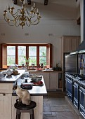 Modern farmhouse kitchen with antique chandelier and cat sitting on bar stool