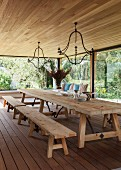 Dining room with rustic table, benches and glass walls with view of garden
