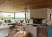 Gemütliches Wohnzimmer mit offenem Kamin, modernen und Vintage Möbeln und einem prachtvollen Blick in die Landschaft