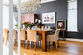 Elegant dining room with anthracite walls, long dining table and upholstered armchairs; pretty sea glass chandelier above table
