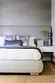 Comfortable double bed with silver-coloured headboard against grey wall; silver grey scatter cushions on bed and silver vase on bedside table