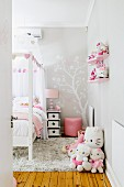 Cheerful girl's bedroom in grey and pink with large collection of soft toys and light wood floor