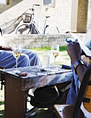Two Africa men sitting in garden outside house with white wine, cigar and magazine