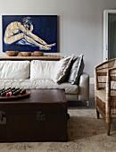 weiße Wohnzimmercouch mit darüberhängendem Aktgemälde; im Vordergrund eine antike Ledertruhe als Couchtisch und ein einfacher Rattan-Armstuhl