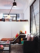 Cosy corner of loft apartment next to white partition with collection of shoes arranged on top