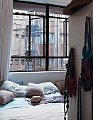 Double bed in bedroom with view of fire escape and windows of neighbouring building through industrial window