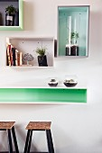 Decorative, wall-mounted shelving units above long shelf used as counter and bar stools