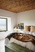 Simple, white bedroom with sea view, rustic bamboo ceiling and old wooden trunk at foot of double bed