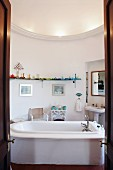 View through double doors of free-standing bathtub in centre of round bathroom