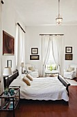 Bedroom with draped white curtains, collection of pictures on walls and colonial-style double bed