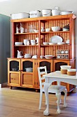 White-painted, ball-and-claw-foot kitchen table and matching chair in front of dresser of reddish wood in rustic dining room