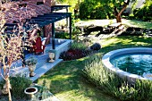 Round pool in garden next to terrace with pergola and house with brick facade