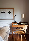 50s wooden chair at delicate writing desk against wall and framed drawings above bed
