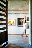 Artworks displayed on wall under spotlights