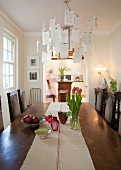 Long wooden dining table with runner of ecru linen and antique chairs; Zettel'z chandelier above table