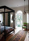 Black four-poster bed with artistically turned bedposts in bedroom with open balcony door and view of garden