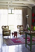 Regal armchairs in front of glass wall in living room with fine rug, collection of glasses on vintage table and studio standard lamp
