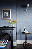 Black fire surround against grey wallpaper; picture with wide silver frame on wall above mantelpiece
