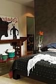 Schlafzimmer mit brauner Trennwand und antikem Wandtisch mit moderner Malerei; auf dem Nachttisch eine silberne Vase mit roten Blumen
