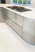Detail of modern, curved kitchen counter with gas hob in white worksurface