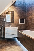 Modern bathroom with tiled walls, sloping ceiling and skylight in architect-designed house