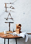 Hand-crafted wall decoration of letters made from old cutlery; cloth, stacked toast and glass of milk on round table