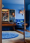50s bar cabinet with mirrored doors and 70s, gilt chandelier above blue velvet sofa in living room with blue walls